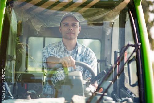 Poster Smiling farmer driving an harvesting machine