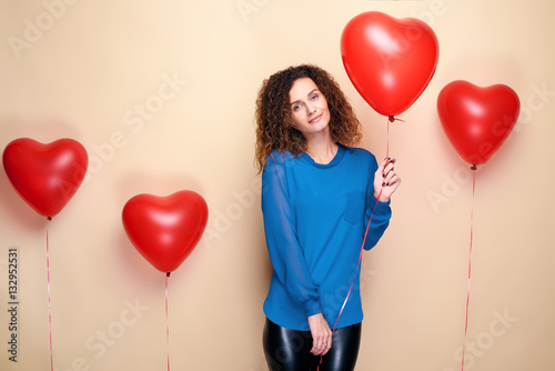 Poster Beautiful young girl with curly hair and blue sweater holding a few red heart air balloon and smiling