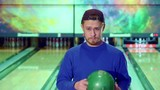 Young caucasian man gesturing ok at the bowling. Bearded guy in cap throw the ball from one hand to another. Attractive guy standing against background of lanes
