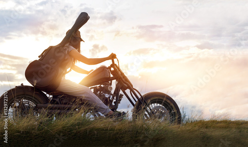 Guitarist woman riding a motorcycle on the countryside road, sunset background