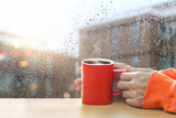 Red coffee cups in hands on a window glass of raindrops background