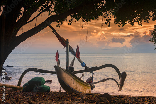 Aluminium Bali Balinese Traditional Outrigger Fishing Boat. A Balinese fishing boat, called a jukung, on the beach in the Amed area of eastern Bali during a glorious sunrise.