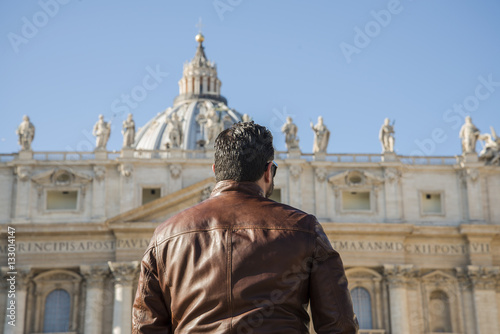 Poster boy shot from behind in front of Saint Peter in Rome