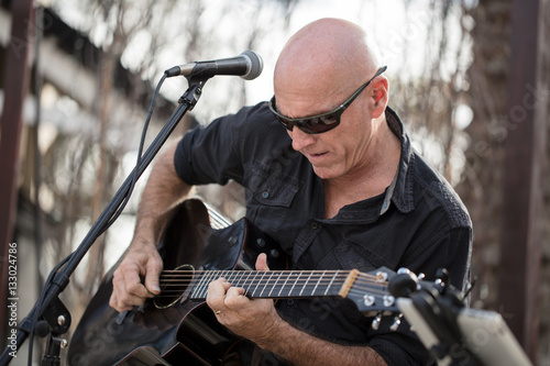 Poster Musician playing guitar at an outdoor venue