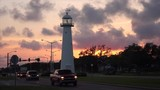 Lighthouse at sunset as cars drive past in Biloxi, Mississippi