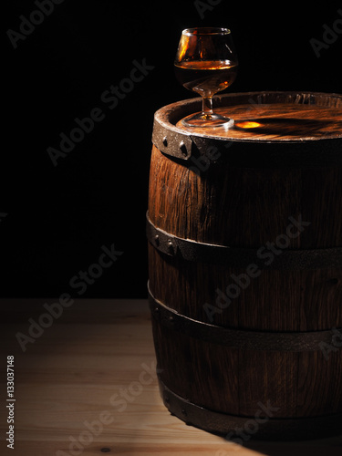 Poster Glass of cognac with barrel on wooden backgroun
