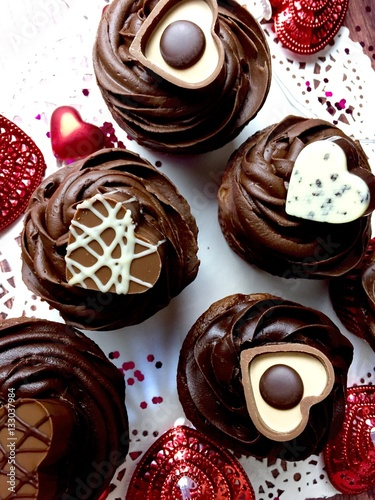Poster Chocolate cupcakes with  heart shaped candies on a festive Valentine's day them