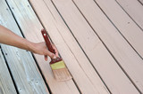 handyman painting the wooden deck with brush