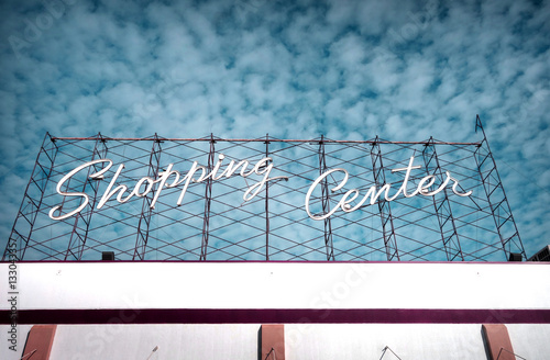 neon shopping center sign and cloudy sky