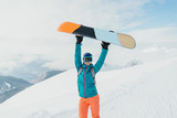 Happy young woman snowboarder