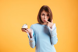 Attractive seductive young woman licking her finger and holding cupcake
