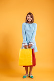 Happy cute young woman standing and holding shopping bags