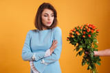 Angry offended woman standing and receiving bouquet of flowers