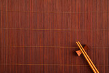 Two chopsticks on a bamboo mat.