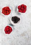 hallon, röda vinbär och björnbär i skolar, ovanifrån på marmor bord