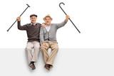 Joyful seniors with walking canes sitting on a panel