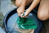 hands washing shirt in basin