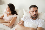 unhappy couple having conflict in bed at home