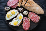 Wooden serving board with salami and fried quail eggs bruschetta