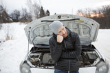 Man problem close to the broken car in winter