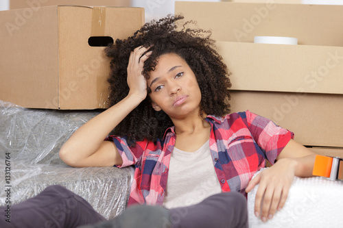 Poster woman moving into new apartment house is bored and tired