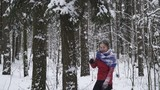 Young woman in a red sweater shake down the snow with a tree in the winter forest and smiling