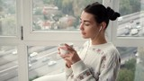 Charming young woman in earphones sitting near window listening musik and drink coffee