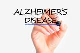 Woman hand writing Alzheimer's disease on screen