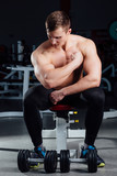 professional fitness bodybuilder sitting on the bench and demonstrates muscles of your body after a workout, at gym.