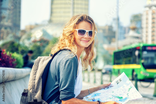 happy young woman with a city map and a backpack smiling