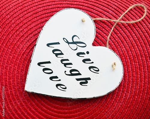 Decorative white wooden heart with the slogan live laugh love on red straw napkin background
