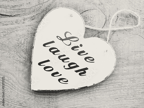 Decorative white wooden heart with the slogan live laugh love on grey wooden background