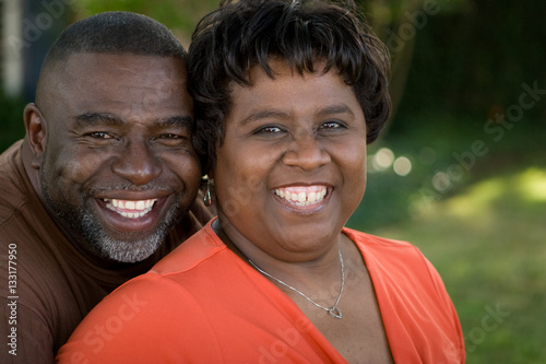 Poster Mature African American couple laughing and hugging.