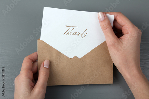 Women's hands with a letter in his hand with the words thank you