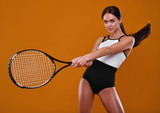 Female tennis player with racket and ball on yellow background