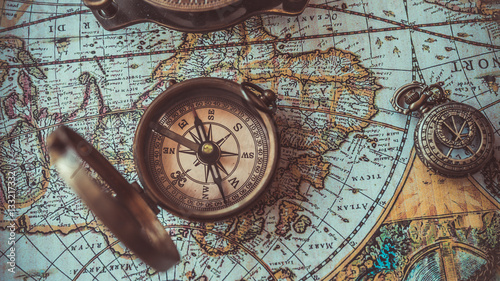Fototapeta Antique bronze emblem compass on a retro world map vintage style.