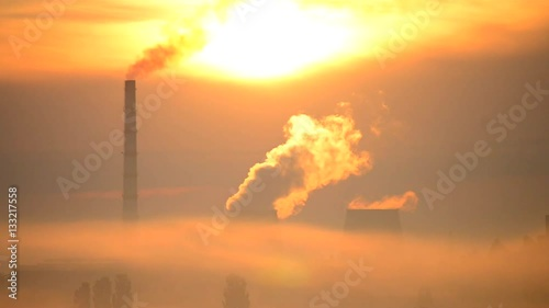 Papiers peints Morning Glory bright cityscape bright urban landscape with a factory and large pipes with smoke at sunrise with bright sun shining