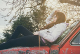 Mujer joven tumbada sobre el capó de un coche oxidado al amanecer
