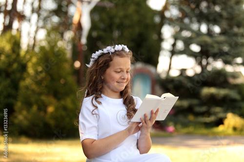 Pierwsza komunia, dziewczynka w białej sukience z książeczką na tle kapliczki Poster