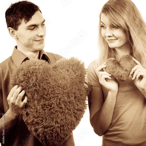 Poster Couple holds red heart shaped pillows love symbol