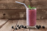 Healthy blueberry smoothie in a glass with berries, mint and straw against a rustic wooden background