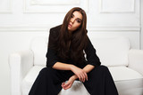 Young fashion model in black jacket sitting on sofa at home