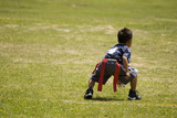 Little boy kid playing flag football on an open field.