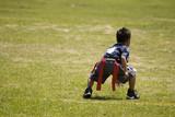 Little boy kid playing flag football on an open field.