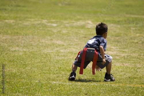 Fotobehang Voetbal Little boy kid playing flag football on an open field.