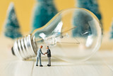 business miniature people make handshaking agreement with light