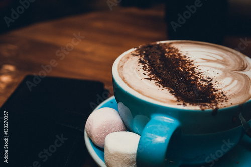 a cup of coffee with foam over wooden table