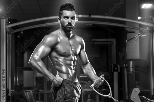 Poster Muscular man working out in gym doing exercises, strong male naked torso abs