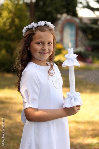 Śliczna dziewczynka w białej sukience trzyma zapaloną świecę. Poster