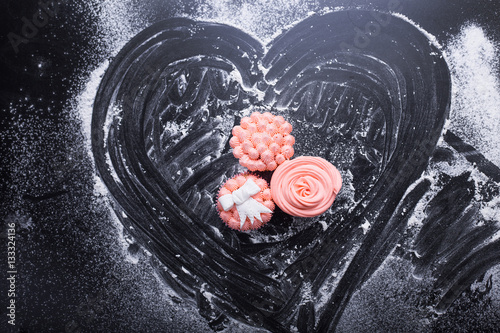 Poster Pink cupcakes on a dark background with flour, top view, pink cream, paste, marm